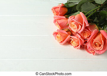 Bouquet of fresh pink roses on wooden background, closeup