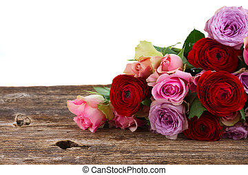bouquet of fresh roses and ranunculus on wood border ...