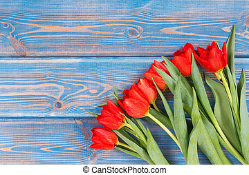 Bouquet of fresh tulips on blue boards, copy space for text