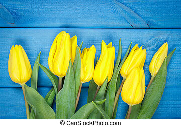 Bouquet of fresh tulips on blue wooden background