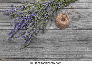 Bouquet of lavender and thread on a wooden table.
