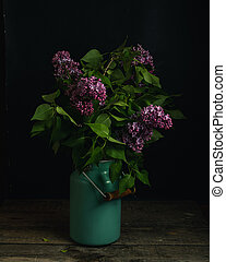 Bouquet of lilac branches on wooden table, dark still life