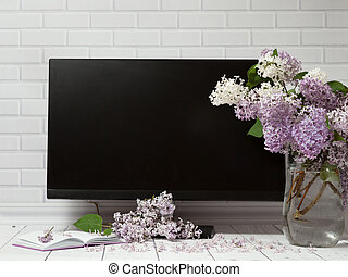 Bouquet of lilac flowers in vase with pad and black monitor