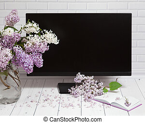 Bouquet of lilac flowers in vase with pad and monitor