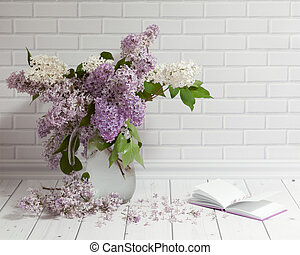 Bouquet of lilac flowers in vase with pad