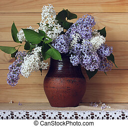 bouquet of lilac in a jug on a wooden background