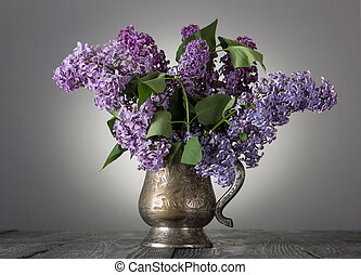 Bouquet of lilac in an old vase, on gray background