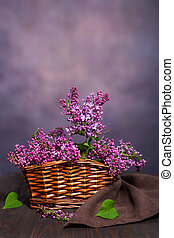 Bouquet of lilacs in a basket stands