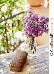 Bouquet of lilacs stands in a bottle next to a loaf of bread on a table on the balcony. Top view