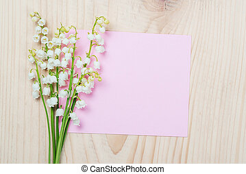 Bouquet of lilies of the valley and empty pink paper sheet on wooden background.