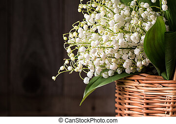 bouquet of lilies of the valley in a wicker basket on a...