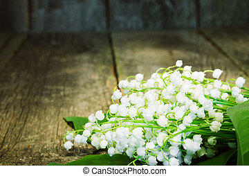 bouquet of lilies of the valley to the blurred wooden background