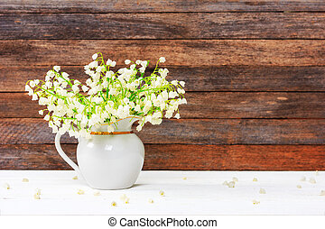 bouquet of Lily of the valley flowers in a jug on a white wooden table on a retro grunge wall background with copy space