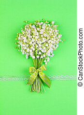 bouquet of lily of the valley flowers with a green bow and ribbon on a green background top view close up