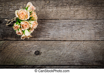 Bouquet of little beige roses on wooden background