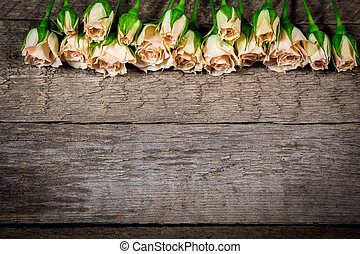 Bouquet of little beige roses on wooden plank