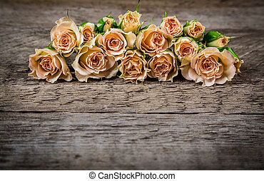 Bouquet of little beige roses on wooden rogue table