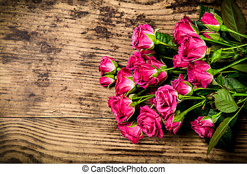 Bouquet of little pink roses on wooden background