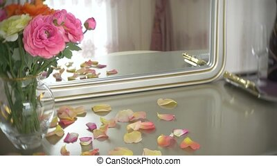 Bouquet of multi-colored roses in a transparent round glass vase is on the table with a mirror. 4k, slow motion