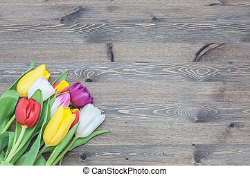 Bouquet of multicolored tulips in a corner on a background of wood.