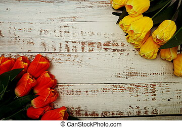 Bouquet of orange and yellow tulips on white wooden background