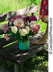 Bouquet of peony flowers in milk can, woamn standing on wooden garden bench