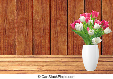 Bouquet of pink and white tulips in vase on wooden table and wooden background