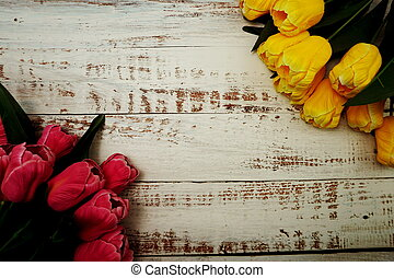 Bouquet of pink and yellow tulips on white wooden background.