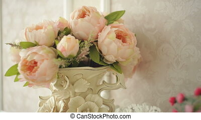 Bouquet of pink peonies in a vase on a table.