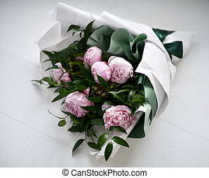 Bouquet of pink peony flowers with green leafs on grey