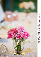 Bouquet of pink ranunculus in vase on wooden background