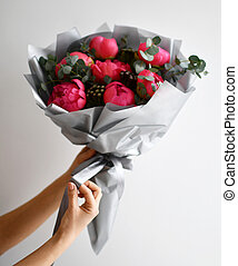 Bouquet of pink red peony flowers with green leafs