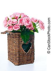 bouquet of pink roses in a wicker basket