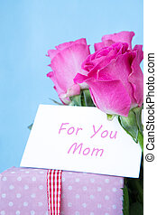 Bouquet of pink roses in vase with pink gift and mothers day card on blue background