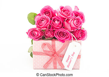 Bouquet of pink roses next to a pink gift with a happy mothers day card on white background close up