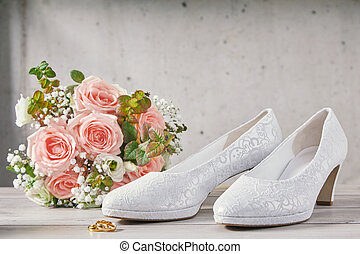 Bouquet of pink roses next to wedding shoes