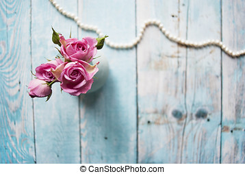 Bouquet of pink roses on a wooden background with the place for your text.