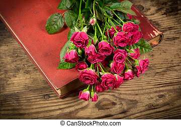 Bouquet of pink roses on old book at wooden table