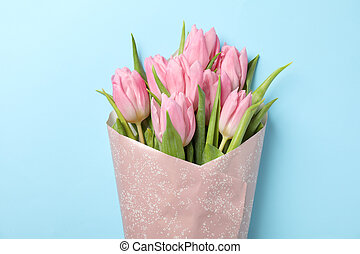 Bouquet of pink tulips on blue background, close up