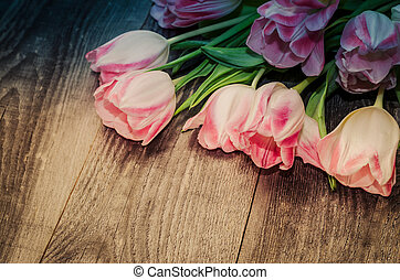 Bouquet of pink tulips on the background of old wooden boards with a place for the inscription, toned