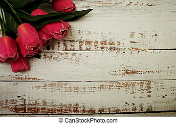 Bouquet of pink tulips on white wooden background