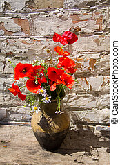 Bouquet of poppies and daisies in clay jug on wooden table against old brick wall