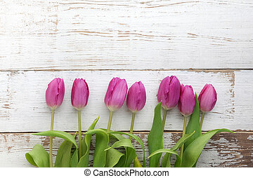 Bouquet of purple tulips on white wooden background.