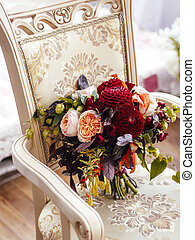 bouquet of red flowers on a vintage chair