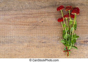 Bouquet of red garden flowers on background old boards