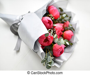 Bouquet of red pink peony flowers with green leafs on grey