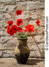 Bouquet of red poppies in clay jug on wooden table against old brick wall