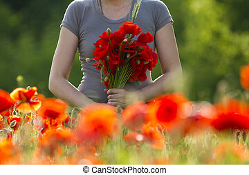 Bouquet of red poppies in the woman's hands
