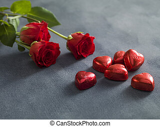 Bouquet of red roses and hart shaped chocolates. Valentines day concept