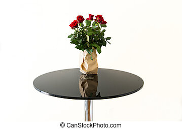 Bouquet of red roses in grey paper vase on black glass table